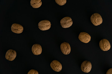 Walnuts in the shell scattered on black surface, top view. Background of round walnuts. Healthy nuts and seeds composition.