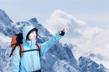 Portrait of adventurous young man on winter mountain top view pointing out. Active lifestyle and tourism.