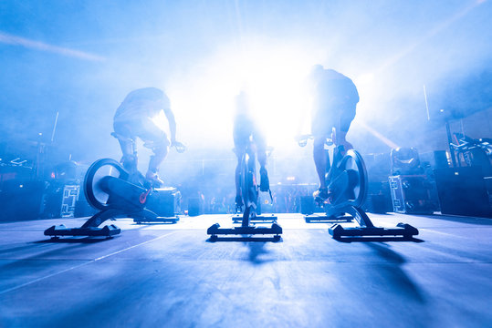 spinning instructors on stage,  before a group of people doing spinning on cycle bike