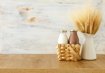 photo of milk and chocolate next to wheat over wooden table and white background. Symbols of jewish holiday - Shavuot