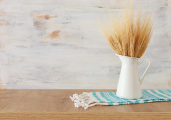 wheat crops and rural kitchen towel over wooden table and white background. Symbols of jewish holiday - Shavuot