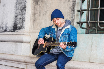 Street Musician in New York City. Young college student with long blonde hair, wearing blue Denim jacket coat, knitted hat, sitting against wall by window on campus, looking down, playing guitar..