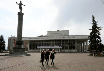 Triplet sisters walk in front of the State Theatre of Opera and Ballet in Krasnoyarsk