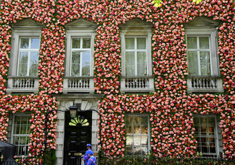 Doormen dressed in floral patterned suits stand on duty outside of private club Annabel's with its front covered in flowers in Mayfair area of London