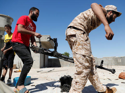 Fighters loyal to Libyan internationally recognised government carry a heavy machine gun during clashes with forces loyal to Khalifa Haftar at outskirts of Tripoli