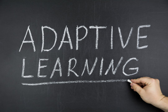 Hand writing topic of Adaptive Learning on black chalkboard