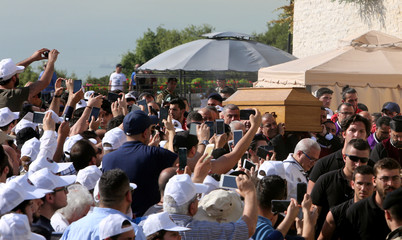 People use their mobile phones to take pictures of the coffin of Cardinal Nasrallah Sfeir, the former patriarch of Lebanon's Maronite church during his funeral in Bkerki