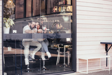 View through the glass of a young couple in love sitting in a cafe and drinking coffee and watching a video about traveling on a smartphone using high-speed free Internet. Travel dream concept