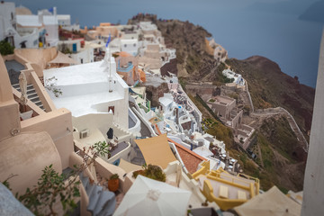 View of byzantine castle ruins and houses of Oia village over red cliffs