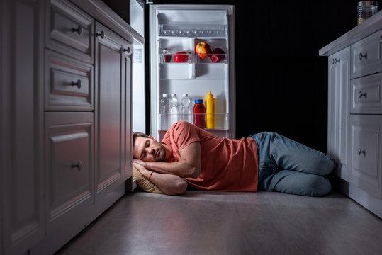 exhausted man sleeping near open refrigerator on kitchen floor
