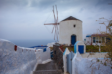 Windmill in the colorful village of Oia on a rainy day
