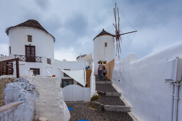 Tourists near windmill in the colorful village of Oia on a rainy day