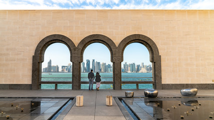 Couple looking at Doha skyline through the arches of the Museum of Islamic art, Doha, Qatar