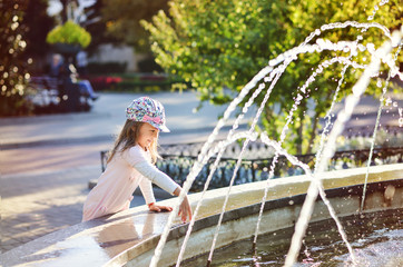 girl playing with fountain water