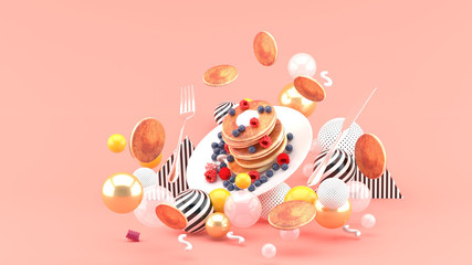 Pancakes and berries among colorful balls on a pink background.-3d rendering.