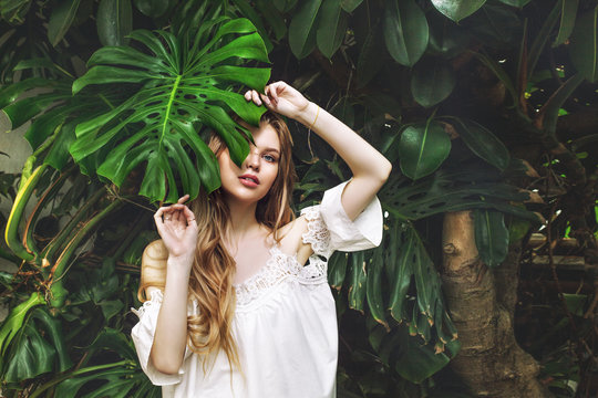 Young beautiful happy blonde girl model on tropical plants background with green leaf