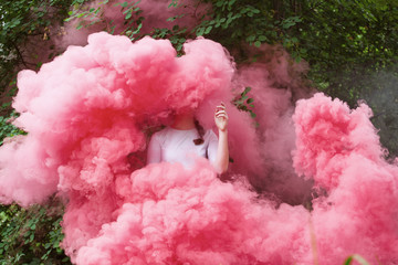 Young woman wrapped in pink smoke