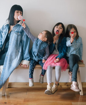 Girls with lollipops with a woman blowing a bubble