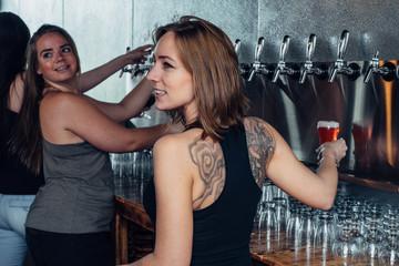Female bartenders serving beer on tap