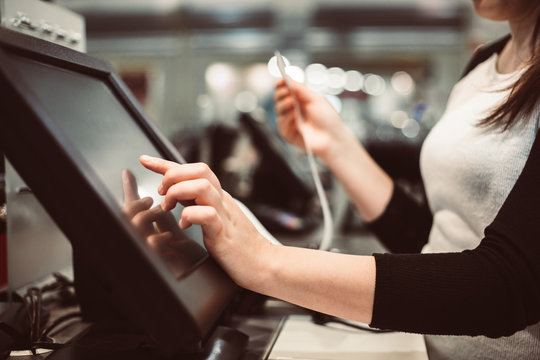 Young woman hand doing process payment on a touchscreen cash register, finance concept (color toned image)