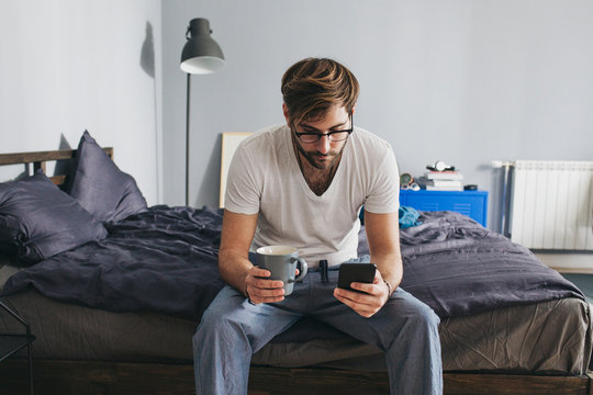 Man Typing on Cell Phone at Home
