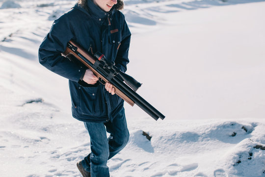 Unrecognizable man walking by the snow with rifle