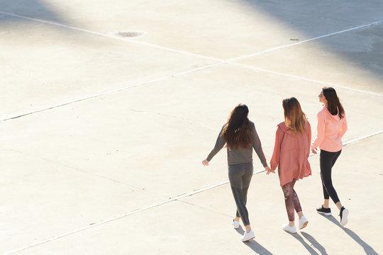 Sportswomen in sportswear walking on sunlit asphalt.