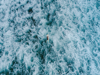 Aerial view of the surfer in the seething ocean