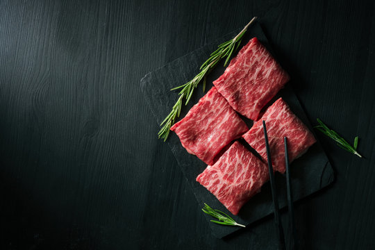 Sliced wagyu marbled beef for yakiniku on plate on black background, Premium Japanese meat, top view and copy space