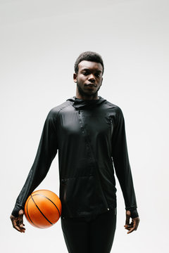 Stylish sportsman standing with basketball