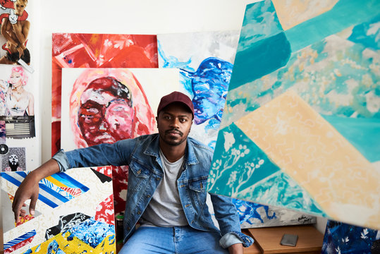 Portrait of proud artist with artwork at the studio.