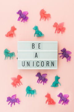 Light box saying Be a Unicorn surrounded by colorful toy unicorns on a pink background