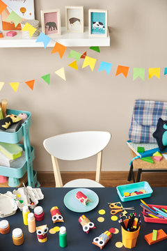 Preschool's table with colorful handmade owls and tools for pain
