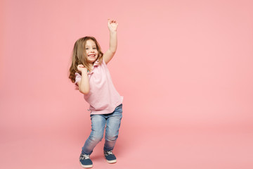 Little cute child kid baby girl 3-4 years old wearing light clothes dancing isolated on pastel pink wall background, children studio portrait. Mother's Day, love family, parenthood childhood concept. Wall mural