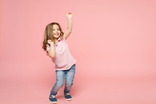 Little cute child kid baby girl 3-4 years old wearing light clothes dancing isolated on pastel pink wall background, children studio portrait. Mother's Day, love family, parenthood childhood concept.