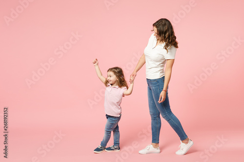 Woman in light clothes have fun with cute child baby girl. Mother, little kid daughter isolated on pastel pink wall background, studio portrait. Mother's Day, love family, parenthood childhood concept