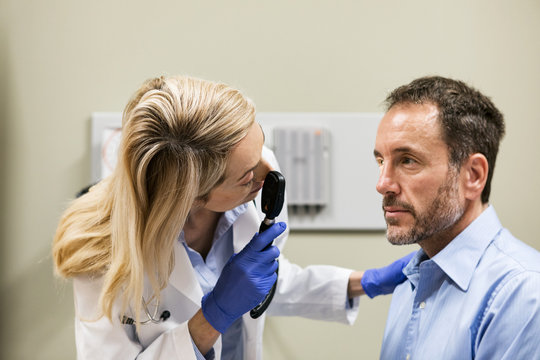 Clinic: Doctor Using Ophthalmoscope To Check Patient