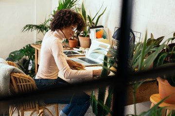 Afro businesswoman working in office full of plants.