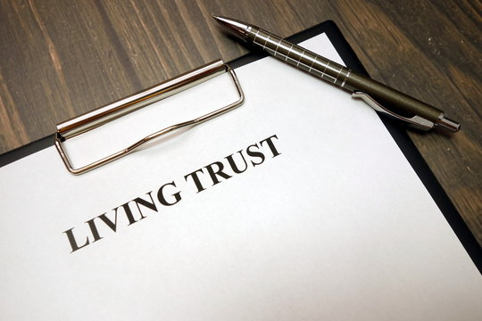 Clipboard with living trust and pen on desk