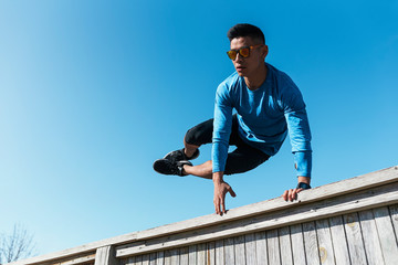 Young asian man practicing parkour in the city.