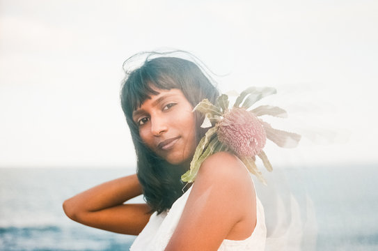 Beautiful Woman with flowers at the beach
