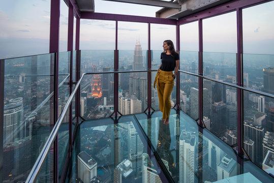 Woman admiring the Kuala Lumpur skyline from a terrace