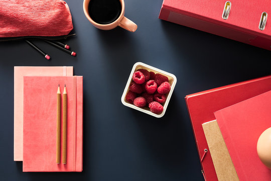 Container of fresh raspberries with notebooks on black desk