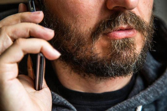 Close up portrait of bearded man talking on smart phone, focus on lips, no eyes, secret talk, criminal threating someone