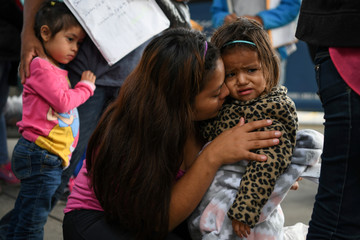 Roselin, an asylum seeker from Honduras, comforts two year-old daughter Julieth as they wait with other migrant families recently released from detention to board a bus in McAllen