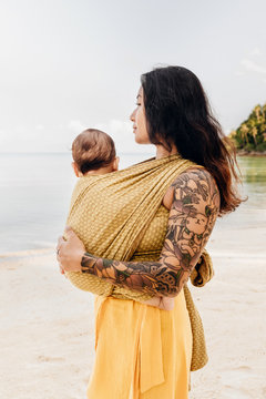 Side view of woman carrying her baby on beach