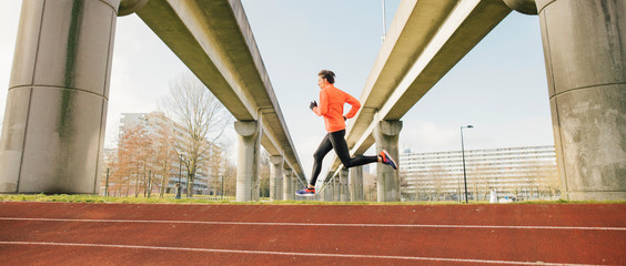 A male runner or athlete running on a urban running track.