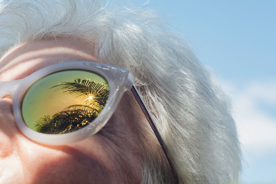 Senior woman with palm trees reflected in sunglasses