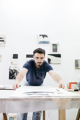 Man with drawings at table