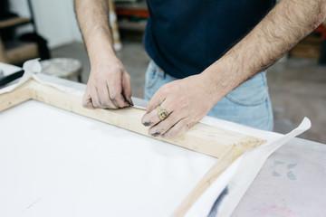 Crop artist fixing linen on frame